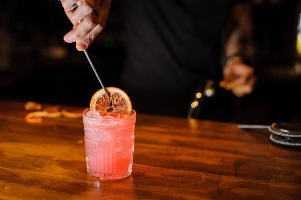 barkeeper arbeiten, und cocktails zuzubereiten - dekorierte schnapsflaschen stock-fotos und bilder