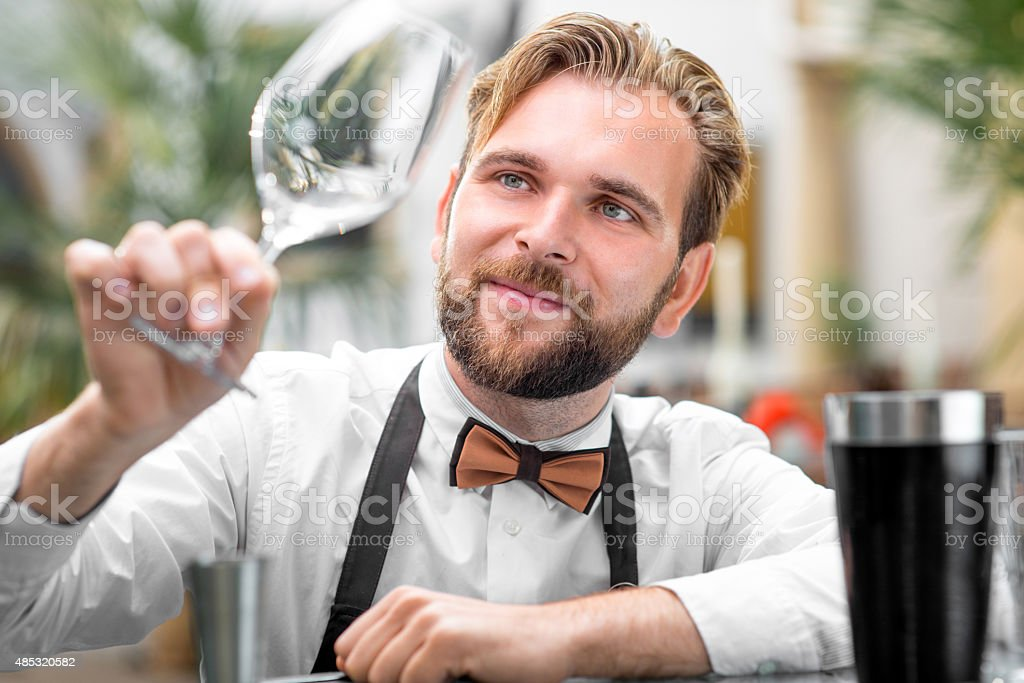 Barman checking the cleanliness of glass stock photo