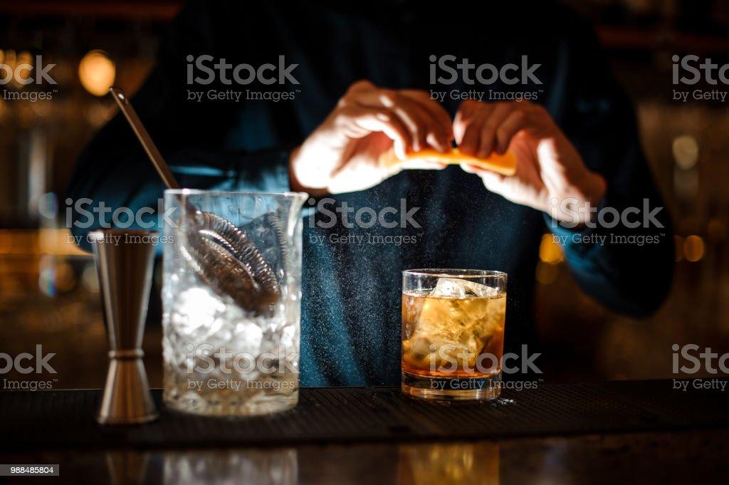 Barmann beendet Vorbereitung einen alkoholischen cocktail Old Fashioned hinzufügen eine orange bitter – Foto