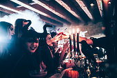 Barman working at Halloween nightclub party giving cocktail to woman in scary costume