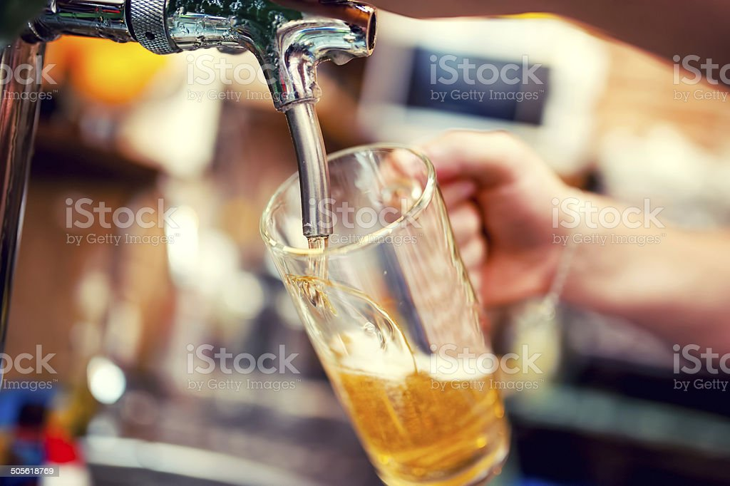 barman hand at beer tap pouring draught lager beer stock photo