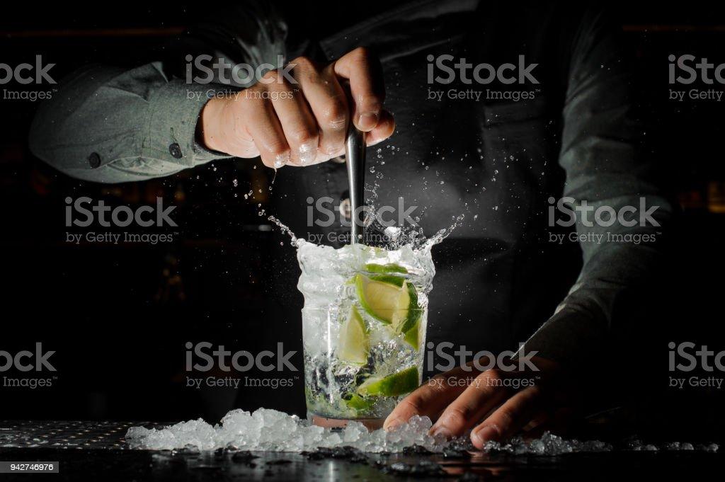 Barmann Hand drückte frischen Saft von Limette macht die Caipirinha cocktail – Foto