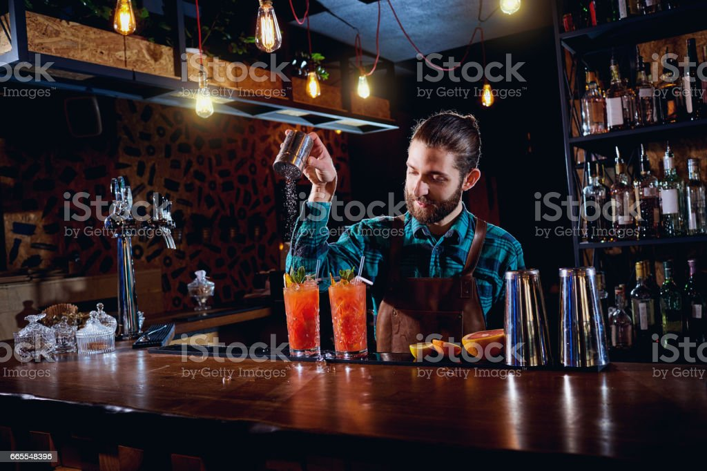 Barman hipster with a beard makes  cocktail in the restaurant ba stock photo