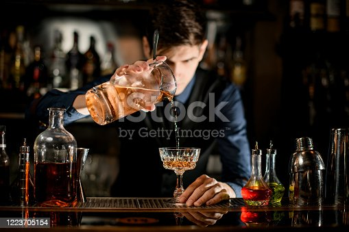 istock Barman holding glass of cocktail and pours it into wineglass. 1223705154