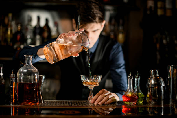 Barman holding glass of cocktail and pours it into wineglass. Young bartender in blue shirt holding glass of cold alcoholic cocktail and pours it into wineglass. bartender stock pictures, royalty-free photos & images