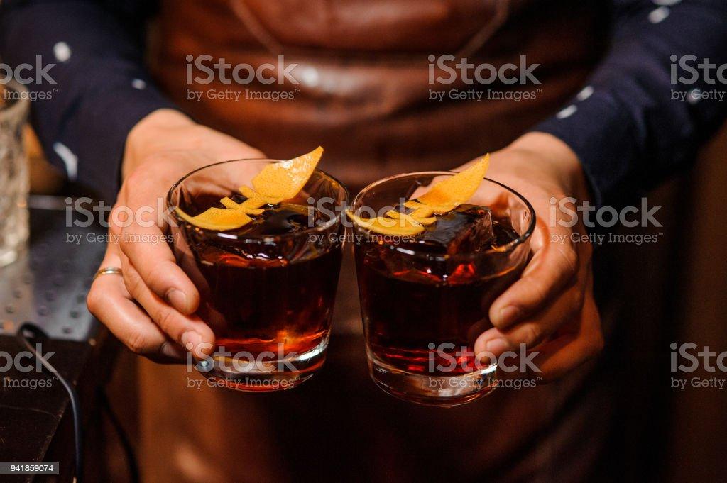 Barkeeper halten zwei Gläser mit alkoholischen Getränken gefüllt – Foto