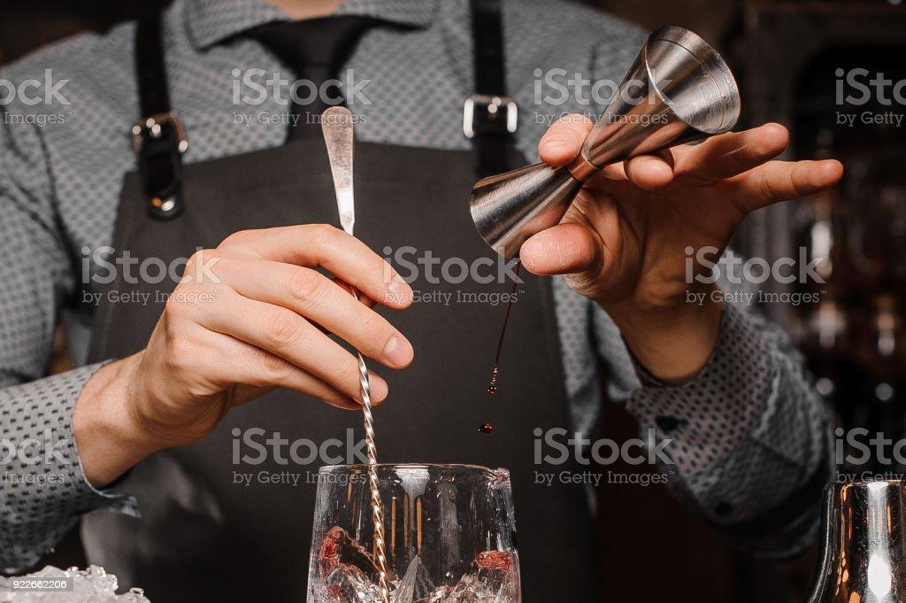 Barkeeper in einem Hemd, Krawatte und Schürze, so dass ein alkoholisches Getränk – Foto