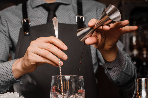 Barman in a shirt, tie and apron making an alcoholic drink Barman in a shirt, tie and apron making an alcoholic drink on the bar counter cocktail shaker stock pictures, royalty-free photos & images