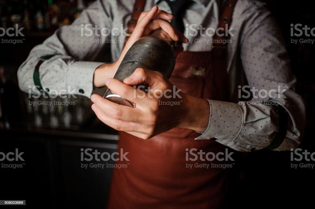 Barman in brown apron shaking the shaker royalty-free stock photo