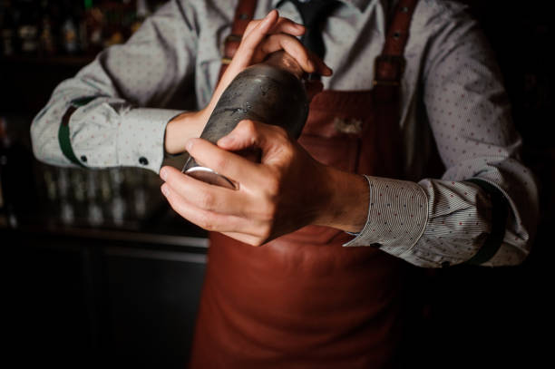 Barman in brown apron shaking the shaker Barman in a brown apron shaking the shaker on the dark background of bar counter bartender stock pictures, royalty-free photos & images