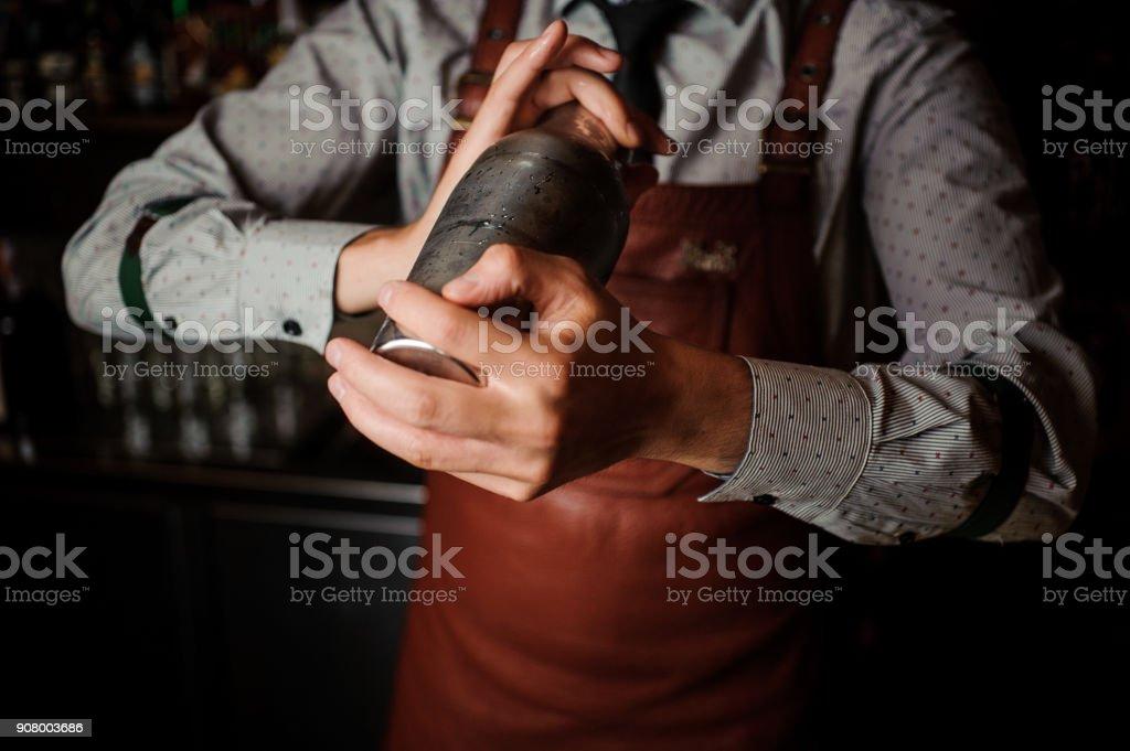 Barman en delantal marrón agitando la coctelera - foto de stock