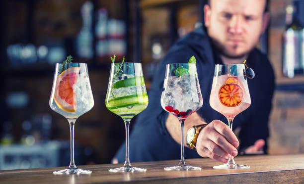 Barman in pub or restaurant  preparing a gin tonic cocktail drinks in wine glasses Barman in pub or restaurant  preparing a gin tonic cocktail drinks in wine glasses. bartender stock pictures, royalty-free photos & images