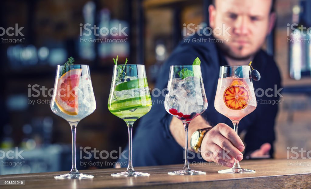 Barman in pub or restaurant  preparing a gin tonic cocktail drinks in wine glasses стоковое фото