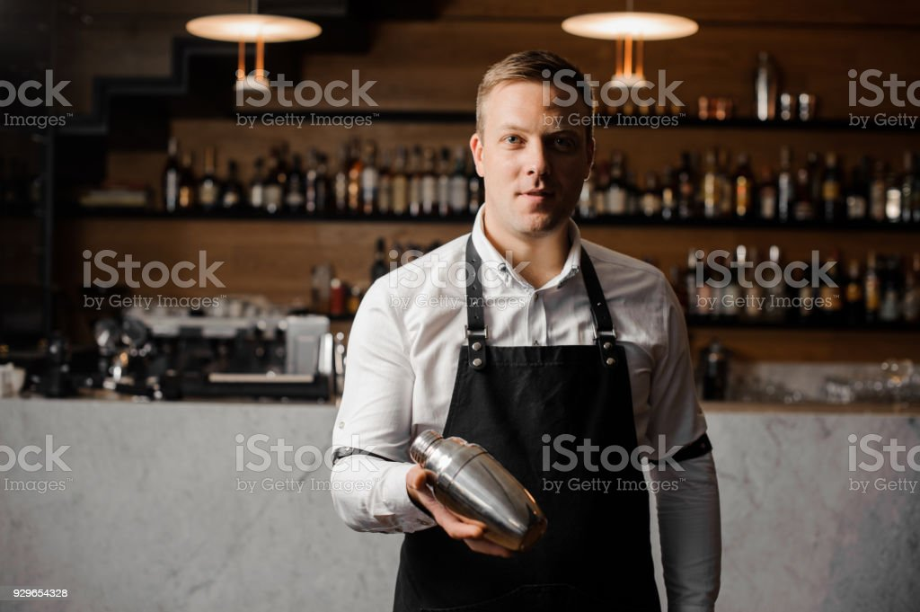 Barman in white shirt and apron holding a shaker stock photo