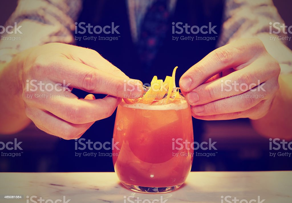 Barman is decorating a cocktail, toned stock photo