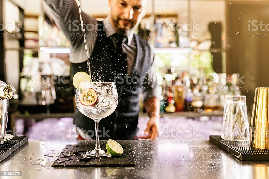 Barman is making cocktail at night club. - foto de acervo