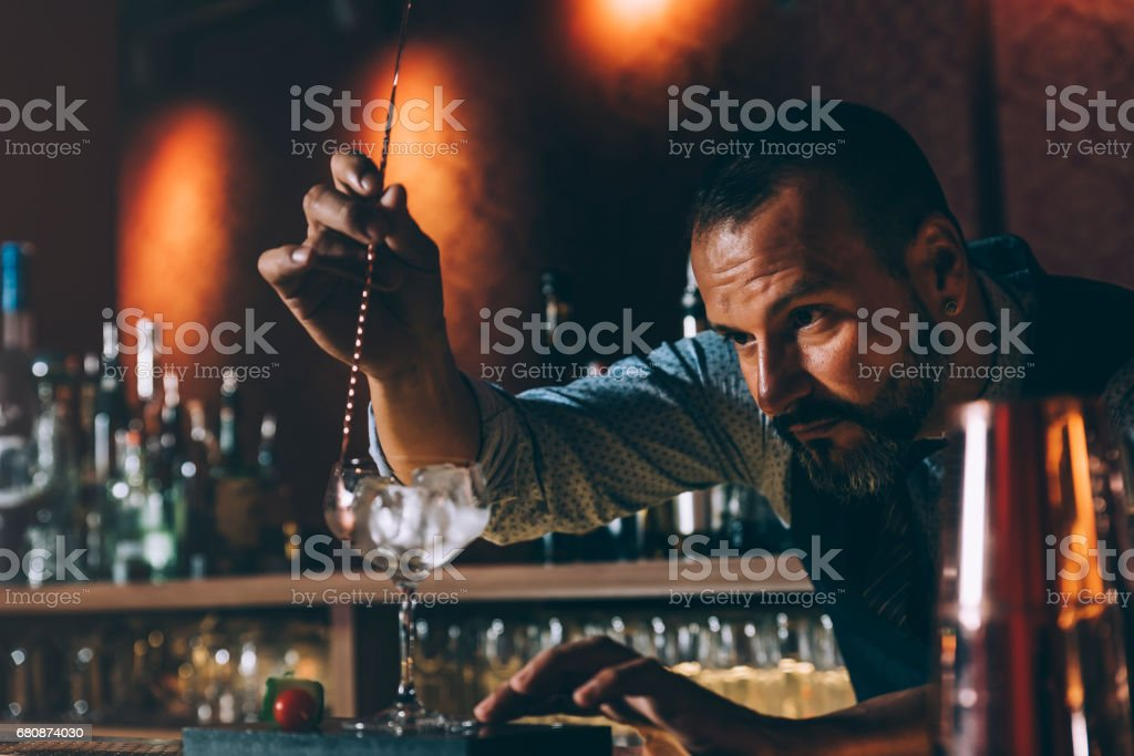 Barman is making cocktail at night club. stock photo