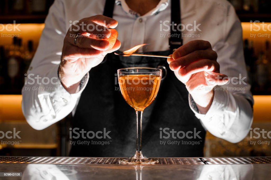 Barman making a fresh alcoholic cocktail with smoky note stock photo