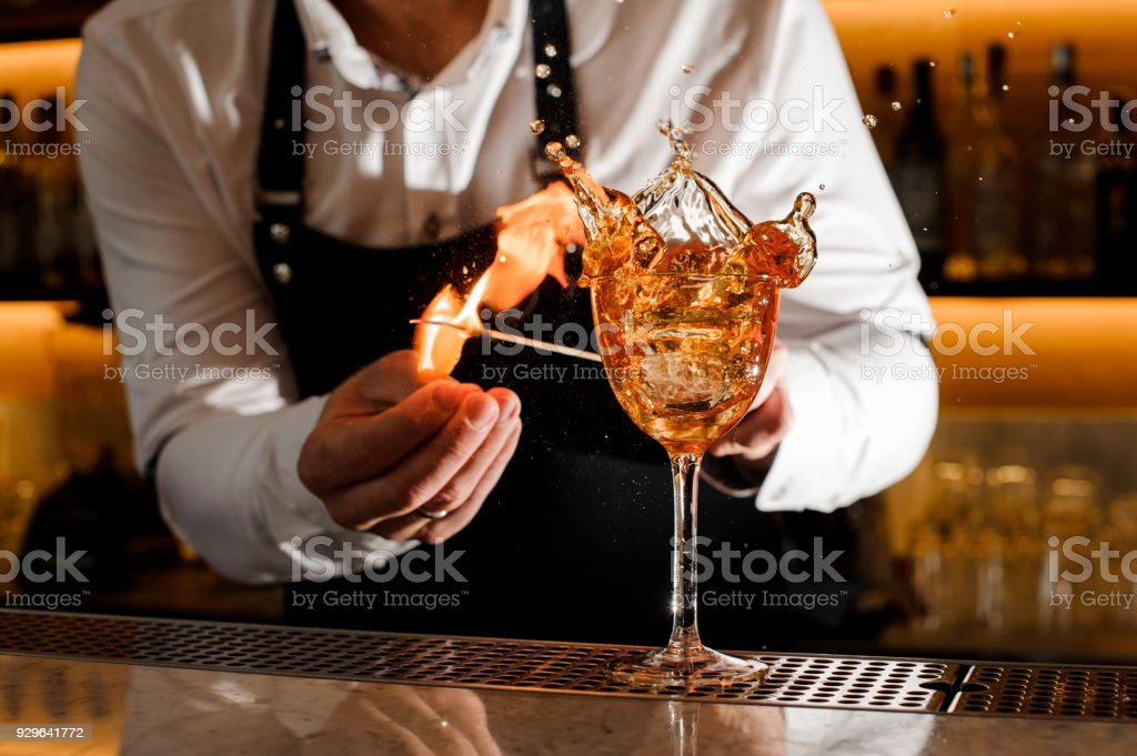 Barman making a fresh burning cocktail with fire stock photo