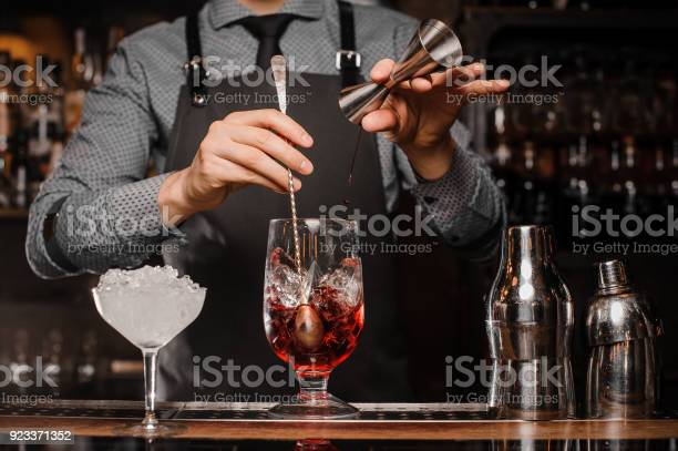 Barman making an alcoholic drink with ice in a cocktail glass picture id923371352?b=1&k=6&m=923371352&s=612x612&h=xa1m i9xht8m77idfh6e9gmvytndudvditbvwjaxhmw=