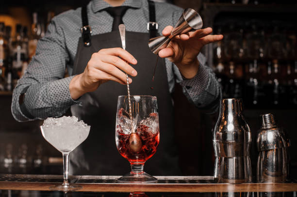Barman making an alcoholic drink with ice in a cocktail glass Barman in shirt and apron making an alcoholic drink with ice in a cocktail glass bartender stock pictures, royalty-free photos & images