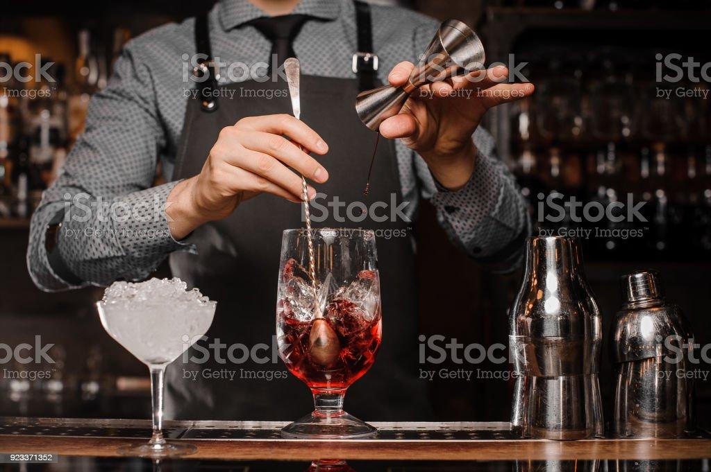 Barman haciendo una bebida alcohólica con hielo en un vaso de coctel - foto de stock
