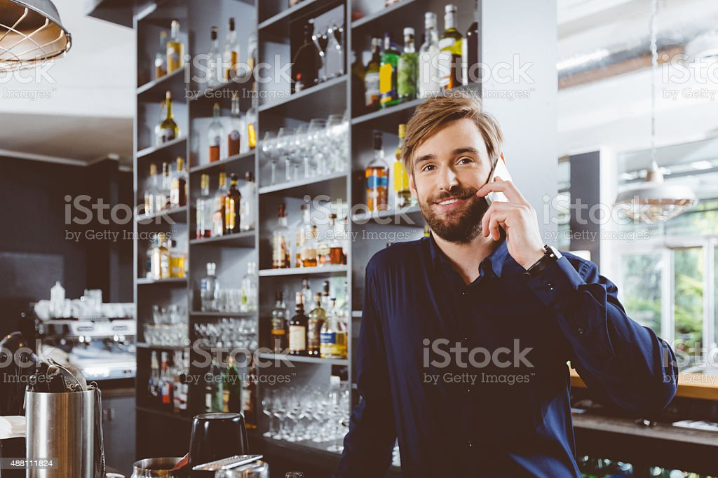 Barman on phone in the pub stock photo