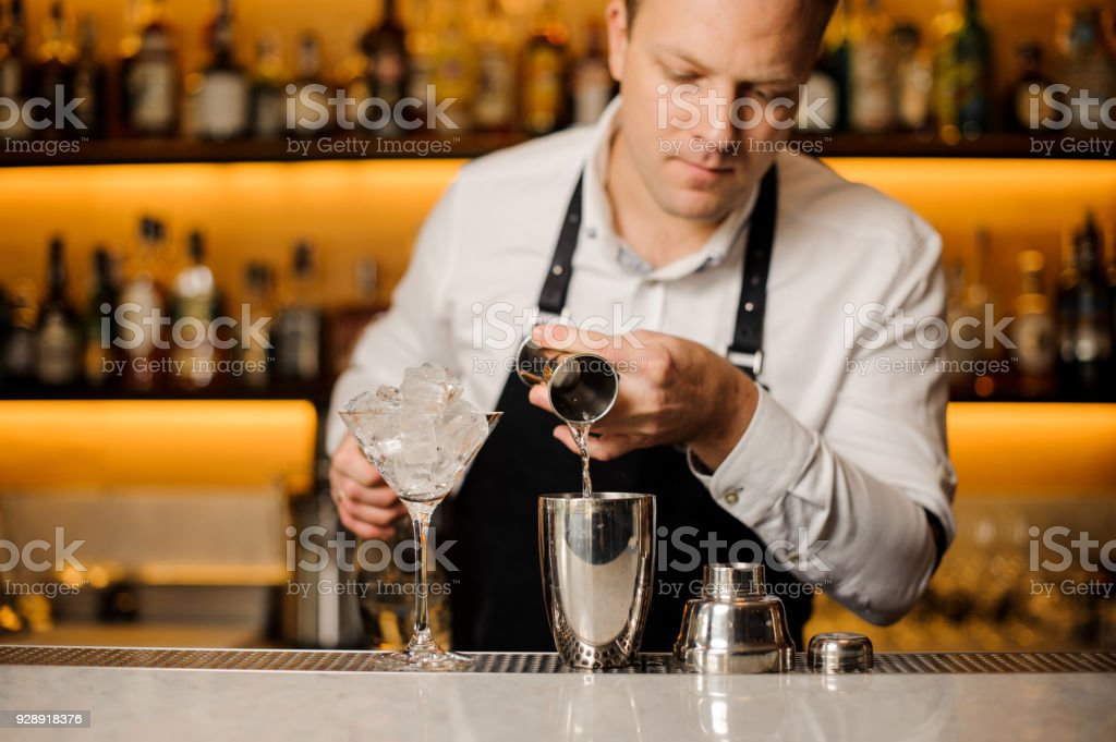 Barman pouring a portion of alcoholic drink into the shaker stock photo