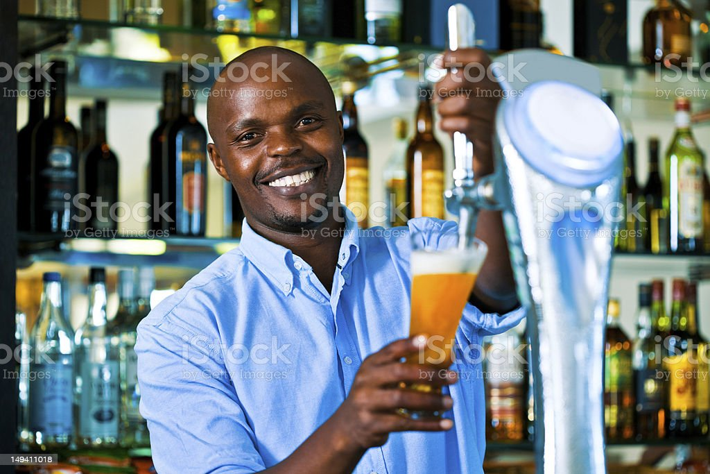 Barman pouring beer Young adult man pouring light beer, looking at camera and smiling. Adult Stock Photo