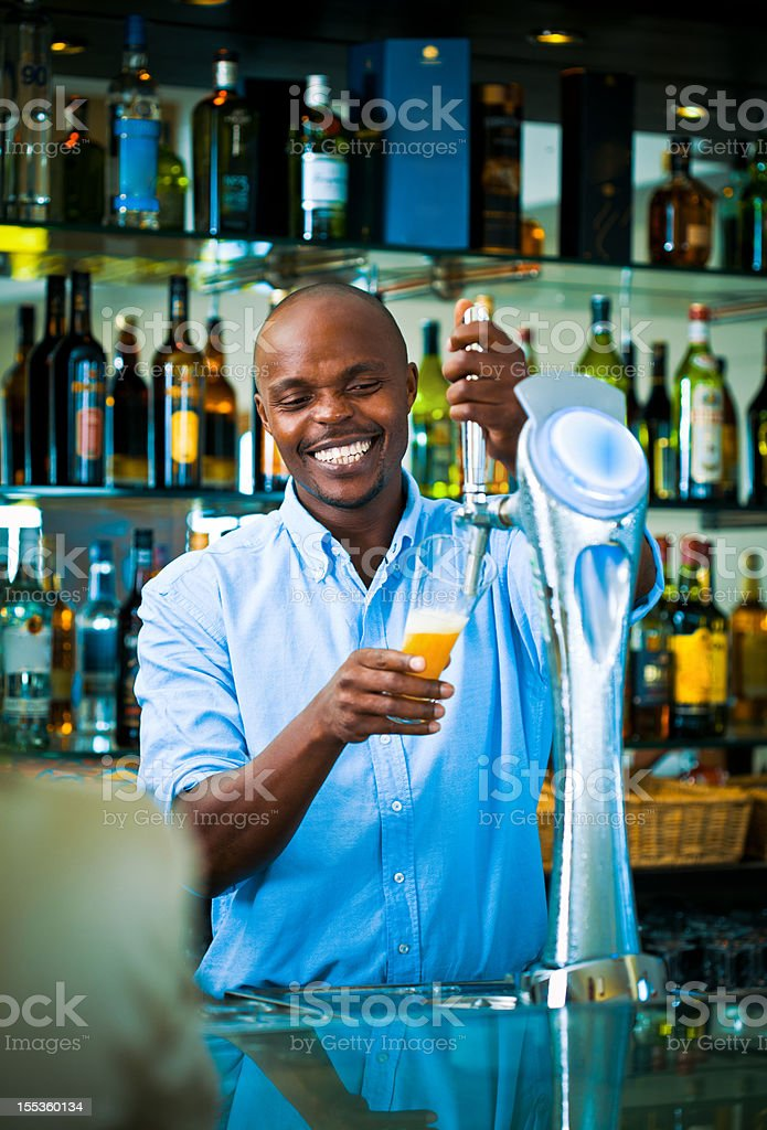 Barman pouring beer Young adult smiling man pouring light beer. Adult Stock Photo