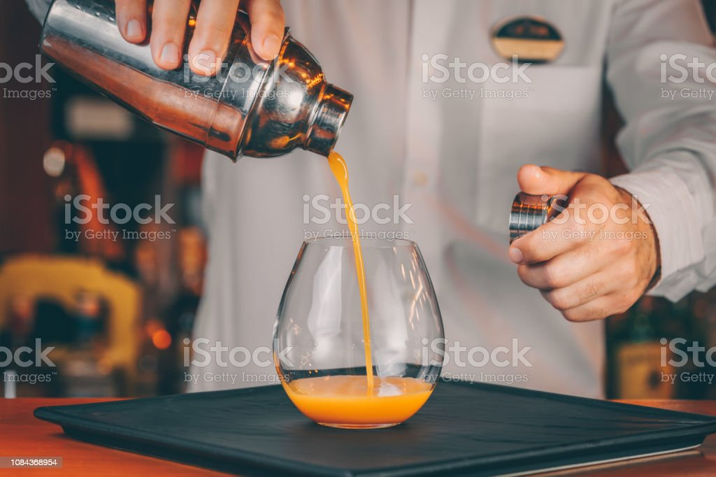 Barman pouring cocktail at a nightclub. Nightlife and entertainment...
