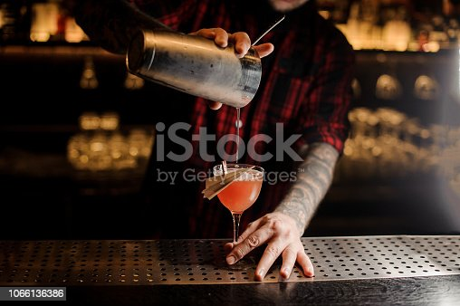 Barman pouring fresh Paper Plane cocktail from shaker into a decorated glass on the bar counter