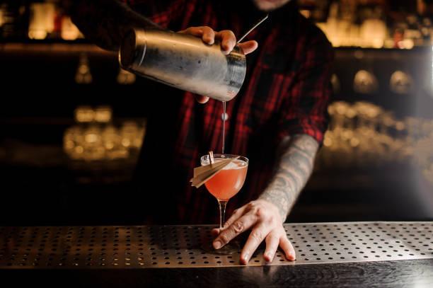 barkeeper gießen frische paper plane cocktail in einem dekorierten glas - goldene bar stock-fotos und bilder