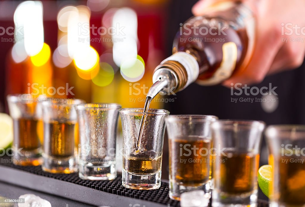 Barman pouring hard spirit into glasses stock photo