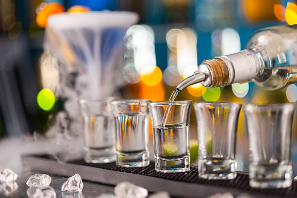 Barman pouring hard spirit into glasses Barman pouring hard spirit into glasses in detail vodka stock pictures, royalty-free photos & images