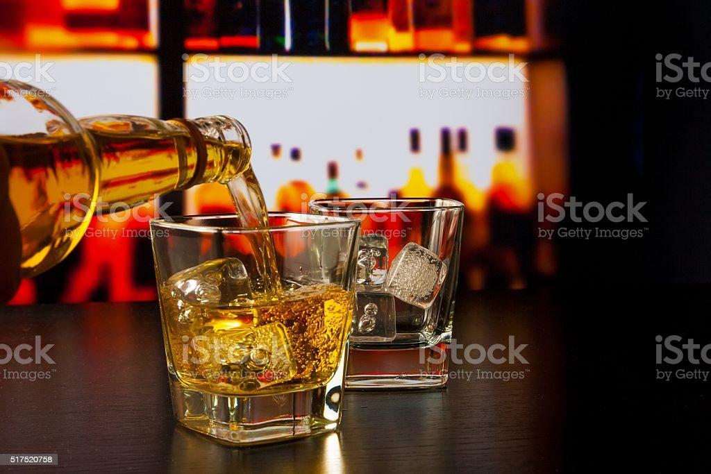 barman servant du whisky dans le verre de whisky et bouteilles - Photo
