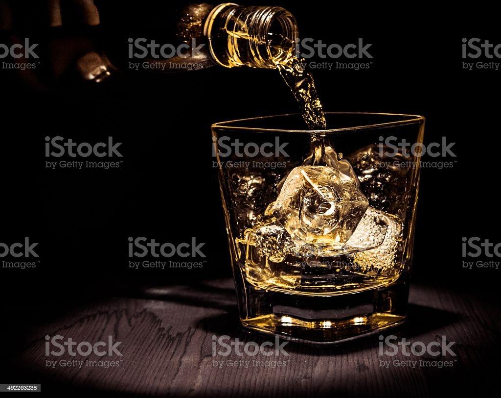 barman à verser dans le verre de whisky sur une table en bois - Photo