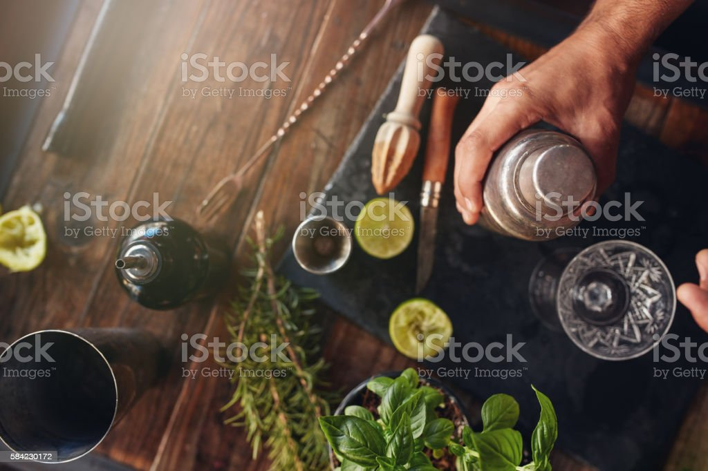 Barman preparing cocktail in shaker stock photo