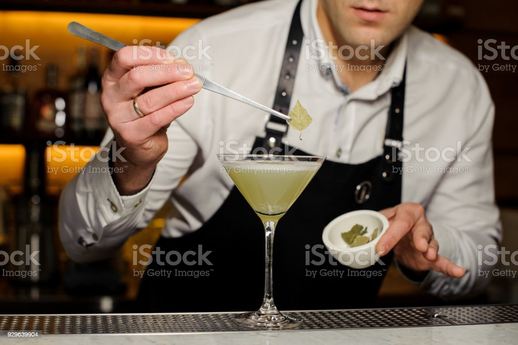 Barman putting a birch leaf decorating an alcoholic cocktail stock photo