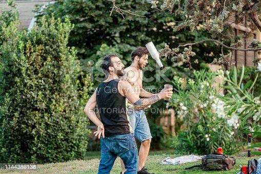 12 JULY 2018, BARCELONA, SPAIN: barman rehearse some tricks in park