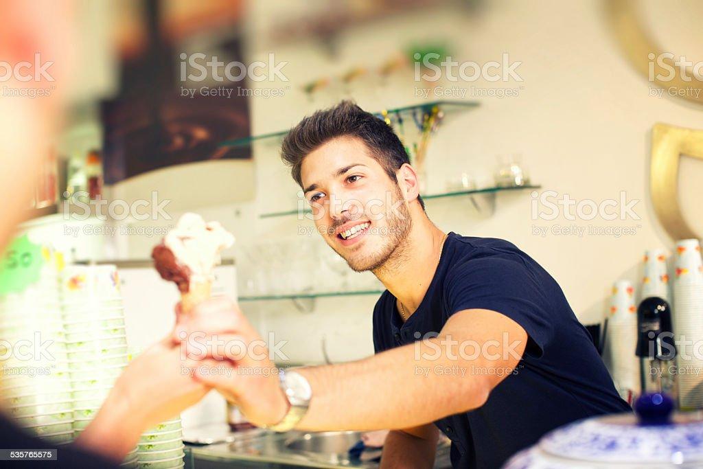 Barman serving a ice cream to customer stock photo