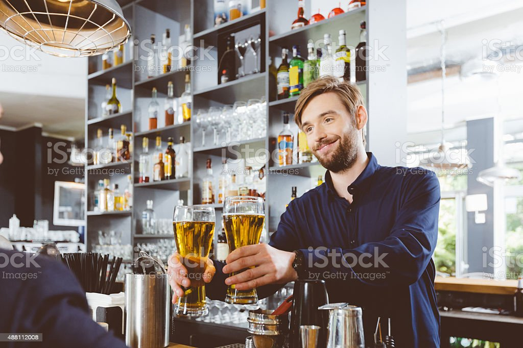 Barman serving beer in a pub stock photo