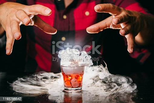 Barman serving smoking orange shot