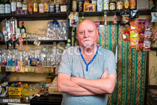 Mature adult barman stood behind the bar of his pub with his arms crossed looking into the camera. Osaka, Japan. May 2016