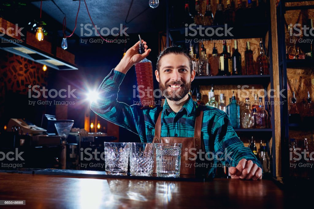 A barman with bottle of alcohol smiles laughing at the bar stock photo