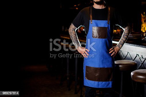 1003493404istockphoto Barman with tattoo on hands dressed in blue and brown apron 989297814