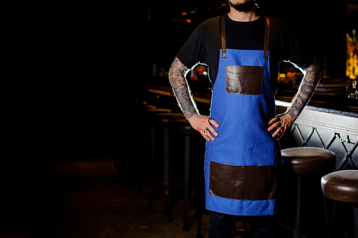 1003493404 istock photo Barman with tattoo on hands dressed in blue and brown apron 989297814