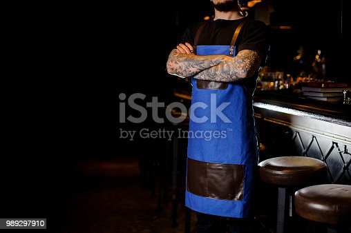 1003493404istockphoto Barman with tattoo on hands dressed in blue and brown apron with crossed hands in night club 989297910