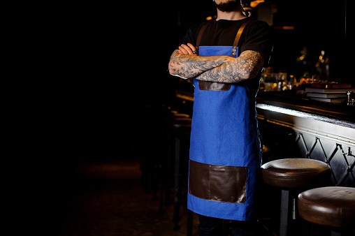 1003493404 istock photo Barman with tattoo on hands dressed in blue and brown apron with crossed hands in night club 989297910
