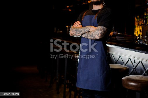 1003493404istockphoto Barman with tattoo on hands dressed in blue apron 989297628